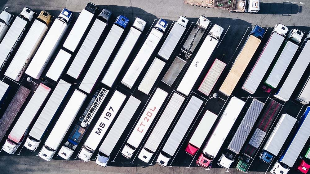Aerial view of trucks parked in a row where truck driver can claim compensation after injury at work while driving