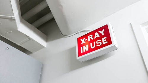 low-angle-shot-of-x-ray-in-use-sign-outside-room-where-medical-examination-is-underway