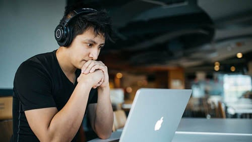 young-man-clasping-his-fist-while-reading-about-covid-19-response-bill-and-workers-compensation-changes-on-laptop